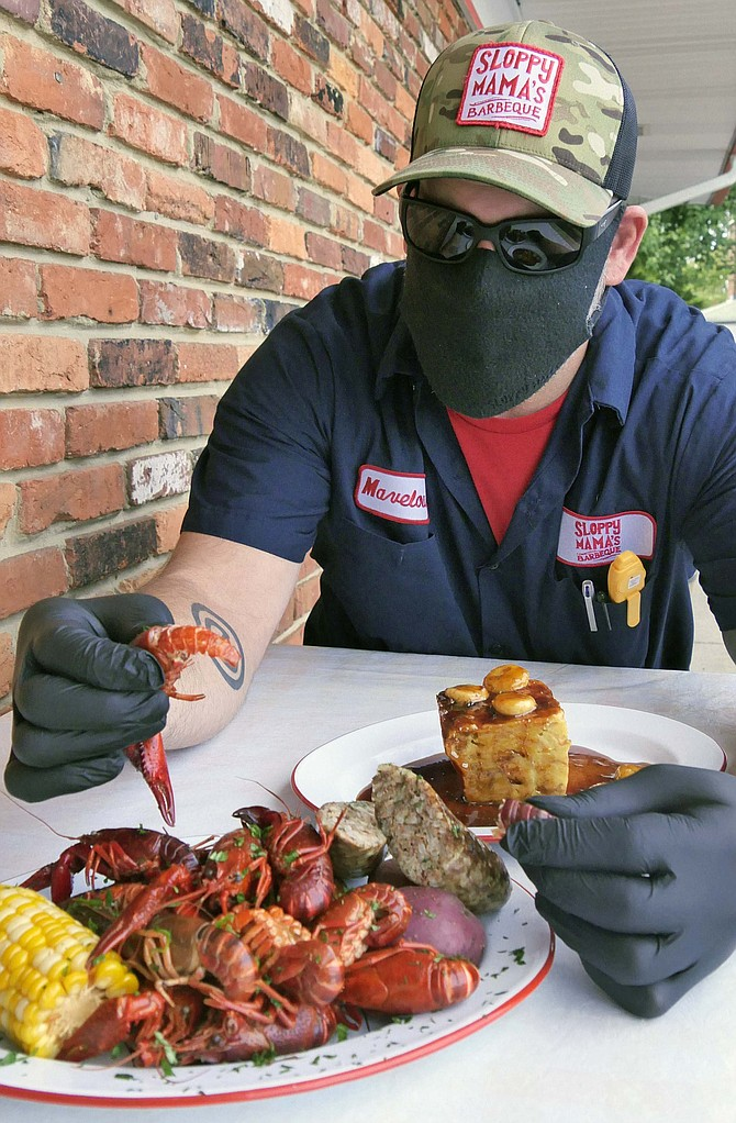 """Joe Newman pulls the tail off a crawfish boiled in a 20-gallon pot of water with potatoes and corn and his own """"happy sprinkles"""" BBQ rub. """"It's all about grinding your own spices, and the ratio makes it what it is."""""""