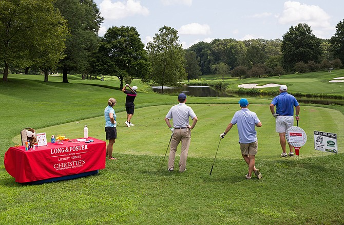 Attendees taking their swing at Hole 11, sponsored by Kari Steinberg of Long & Foster.