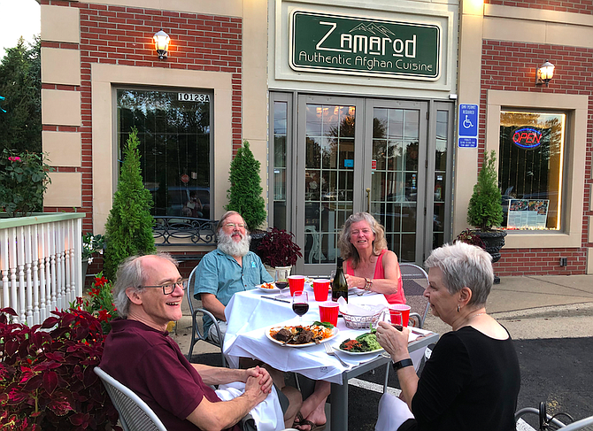 """Two couples enjoy a socially-distanced Thursday evening meal in front of Zamarod. """"We love this kind of food, and we love the owner,"""" said Sue Holberger (back right)."""