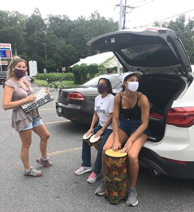 Volunteers Sunny Trippel, left, and Chloe Maciejewski, right, work out a percussion tune with Deb Lang, executive director of KindWorks, with donated instruments. The group held an instrument collection Saturday in Glen Echo. All donations will go to students in need.