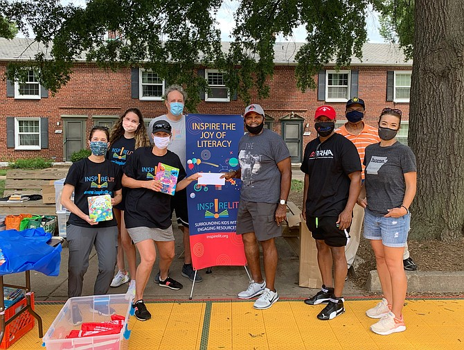 Departmental Progressive Club president Merrick Malone, fourth from right, stands with other volunteers as they prepare to distribute more than 4,000 books donated by the literacy nonprofit InspireLit as part of the Aug. 22 back-to-school drive at the Ruby Tucker Family Center.