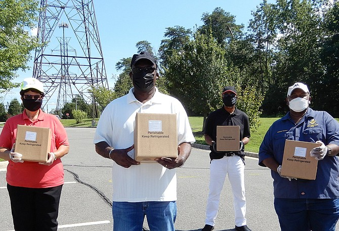 (From left) Mount Olive Baptist Church volunteers Sandra Chew, Roland Williams, Rubin Cuffee and Tony McGhee with food boxes to distribute.