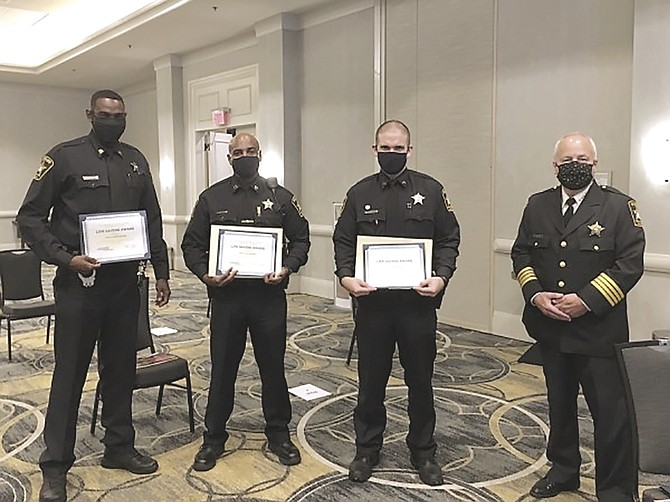 Sheriff Dana Lawhorne, right, stands with Deputy Jason Bebow, Deputy Devon Neckles and Deputy Julio Ocasio after the trio received life-saving awards during the Chamber ALX 2020 Valor Awards Aug. 27 at the Hilton Old Town Alexandria.
