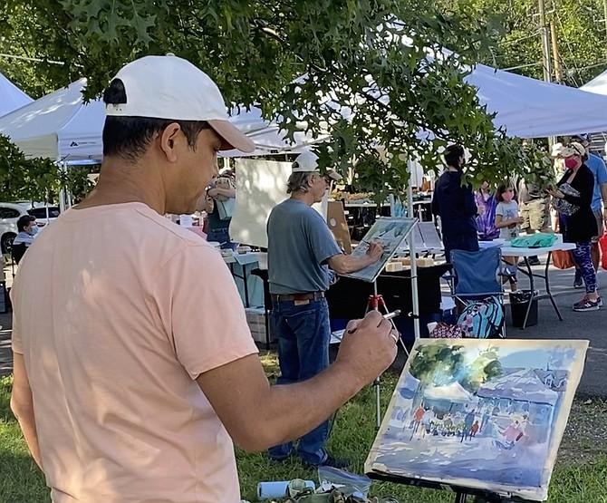 Artists (back to front) Robert Gilbert of Great Falls and Rajendra KC of Falls Church at the Saturday Great Falls Community Farmers Market.