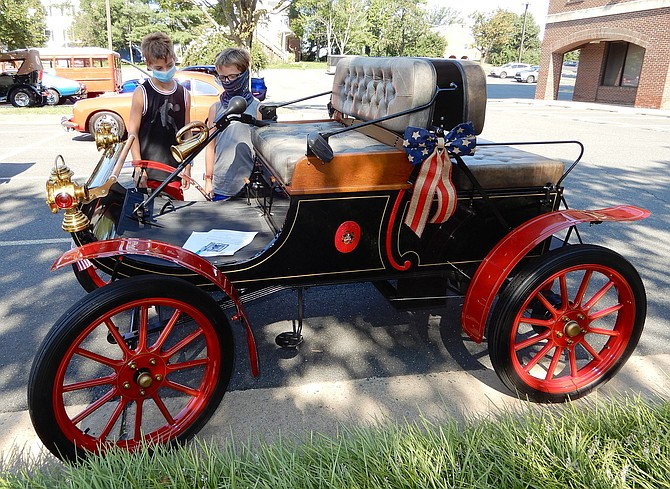 (From left) Ryan Pinchas and Logan Hillman, both 9, check out this 1903 Oldsmobile before the parade starts.