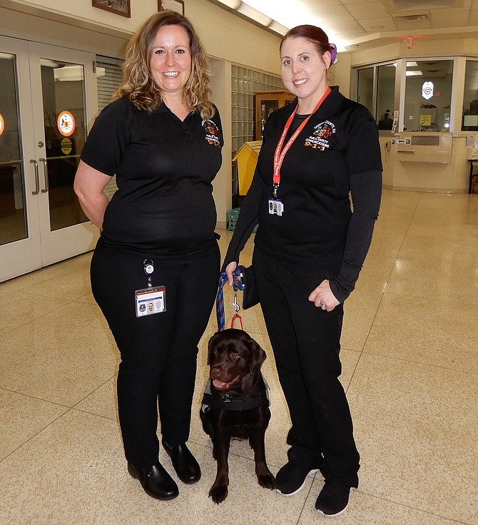 (From left) Fairfax County Public Safety Communicators Marie Keith and Jennifer Heflin with 911 peer-support dog, Sully.