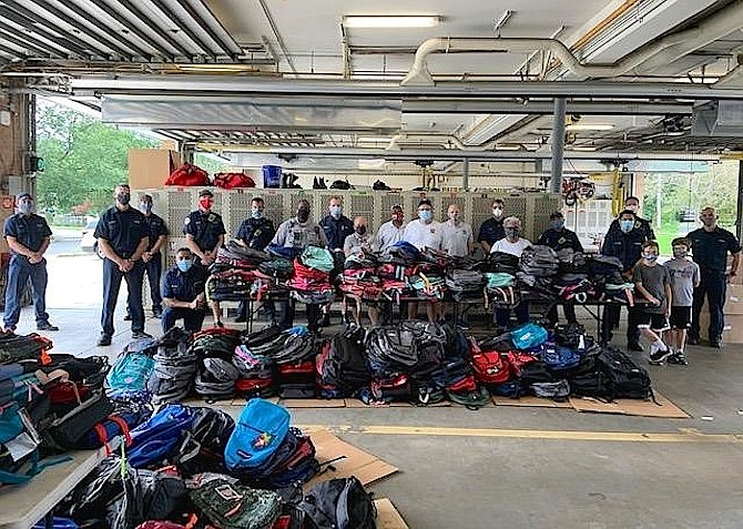 Volunteers gather at Penn Daw Fire Station 11 Aug. 31 to distribute more than 1,100 backpacks filled with school supplies for families throughout the county.