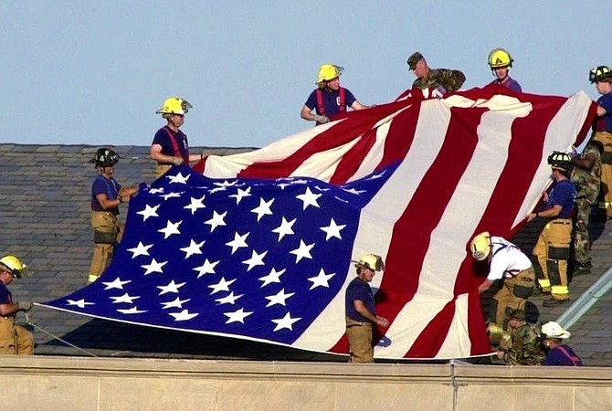 Lt. Jim Morris, far bottom right, and fellow firefighters from Alexandria and Fairfax County Fire and Rescue join soldiers atop the Pentagon to unfurl an American flag during rescue and recovery efforts Sept. 12, 2001. Morris's brother Seth perished in the attacks on the World Trade Center.