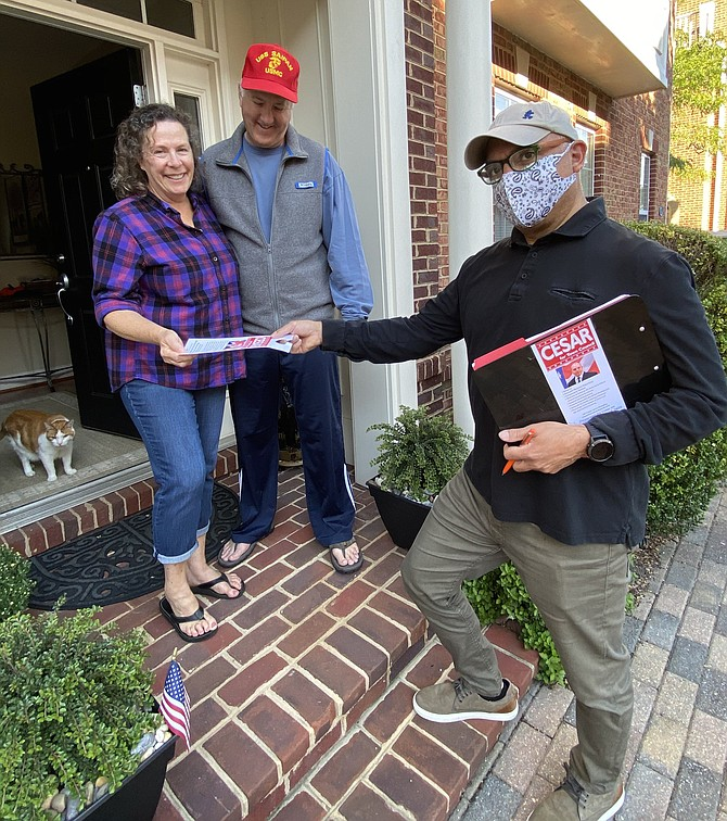 Karen and Paul Novak, voters in the Town of Herndon, take a campaign door hanger from Council member candidate and incumbent Cesar del Aguila. Charlie, the kitty, is all ears.