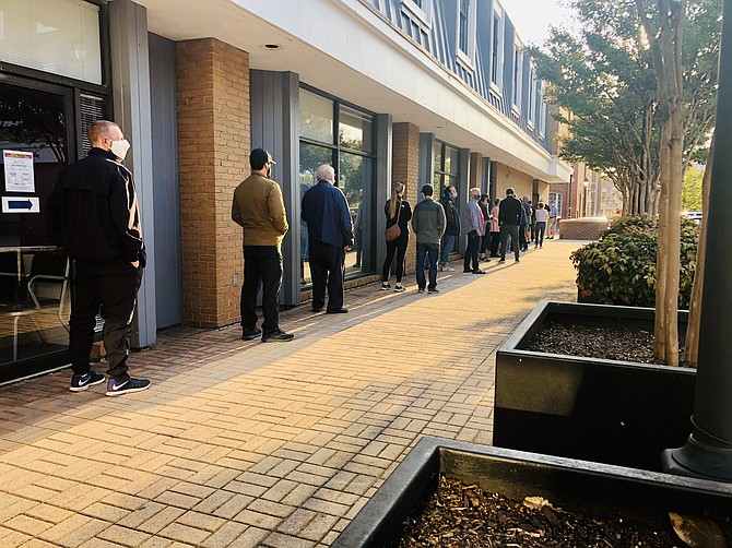 Voters line up outside the registrar's office in Alexandria to cast in-person absentee ballots in this year's election.