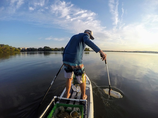 Off the shore in Mount Vernon, Joe Wright scans the river bank for trash within sight of the Mount Vernon Estate.