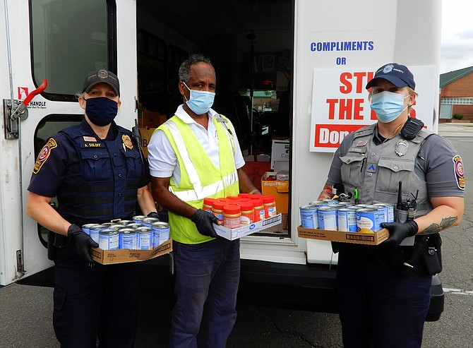 Holding some boxes of donated food outside the Sully District Governmental Center are (from left) Auxiliary Police Officer Ashleigh Soloff, Fastran bus driver Idris Farah and PFC Meg Hawkins of the Fair Oaks District Station.