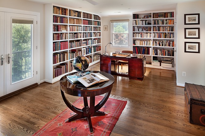 A desk and floor-to-ceiling bookcases allow this space by Keira St. Claire to function as both a library and home office.