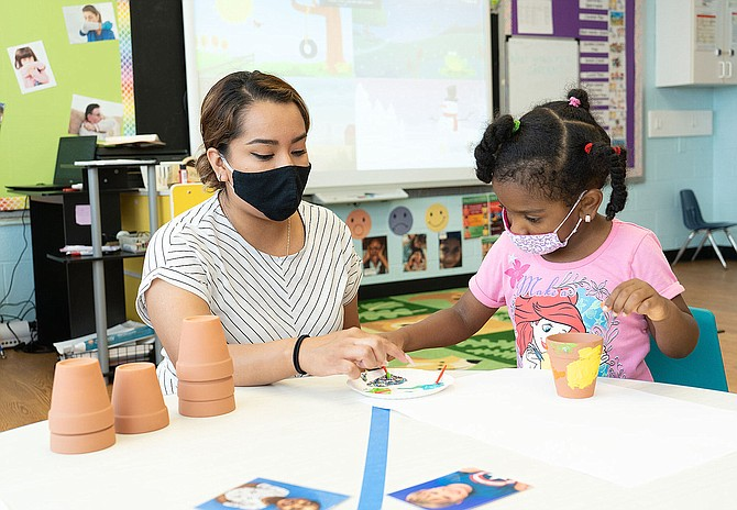 Teacher, Veronica Ruanova, helps a Main Street child with her craft project.