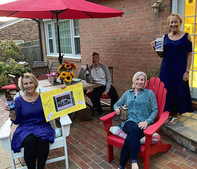 Janet Barnett, left, holds a sign celebrating the Oct. 15 Senior Services of Alexandria Oktoberfest. Barnett hosted an in-home gathering for the virtual event. She is joined by Mitch Opalski of Synergy Home Care, Cecile Garrett of At Home in Alexandria and Pam Phillips of Sunrise of Alexandria.