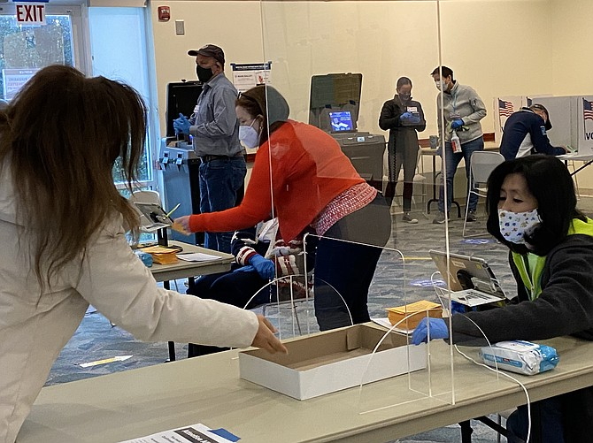 Separated by a plexiglass shield, Fairfax County election official Elizabeth Yang (far right) reaches toward the no-contact box to check the identification of voter at the Great Falls Library polling place.