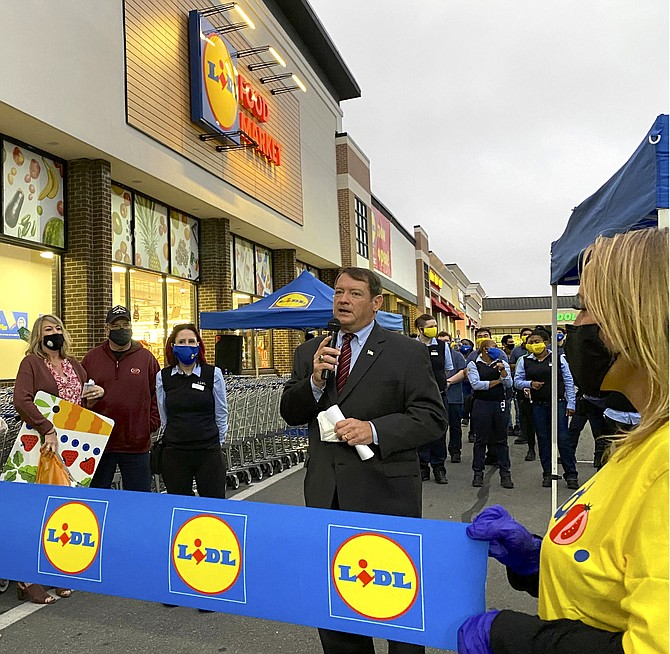 Supervisor Herrity (right) thanks Lidl for investing in the community at the ribbon-cutting ceremony, with (from left) Brooke Freel, Lidl management; first in line shopper; store manager Richelle Thompson, with her store staff in background.