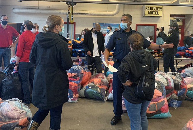 Fairfax County Fire and Rescue Battalion Chief Willie Bailey gives instructions to volunteers at the Oct. 29 Firefighters and Friends coat distribution at Penn Daw Fire Station 11.