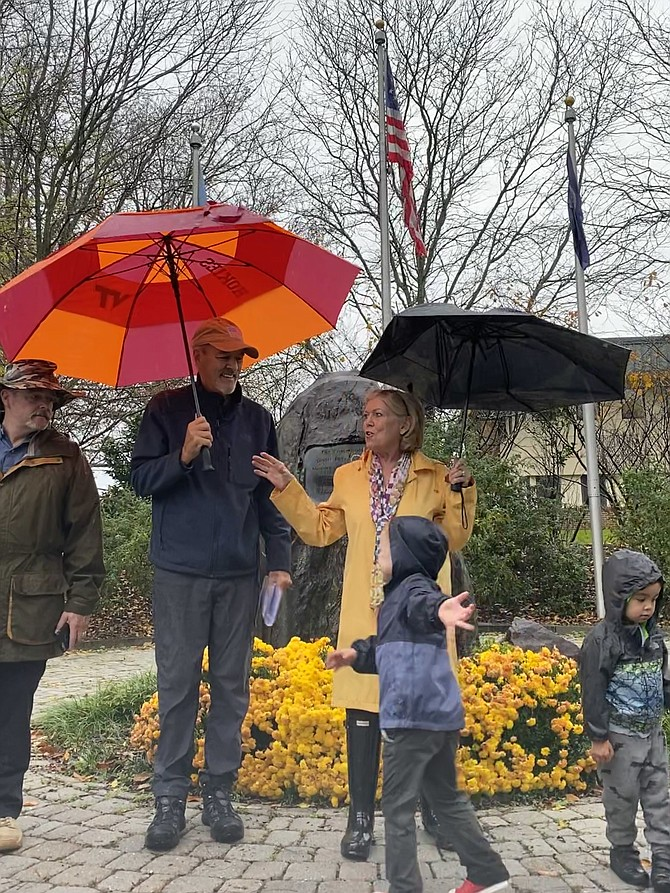 "Nancy Wilson of Great Falls shares a few remarks during the grassroots Veterans Day 2020 ceremony at the Great Falls Freedom Memorial. Executive officers of the Friends of the Great Falls Freedom Memorial, (far left) vice president Dr. John ""Sandy"" Pidgeon, retired Lt. Commander Navy SEAL; and president Andy Wilson, retired Army Ranger officer, listen. The Wilsons' grandchildren, Samuel Cassidy, 4, and Austin Wilson, 3½,  play at their grandparents' feet."
