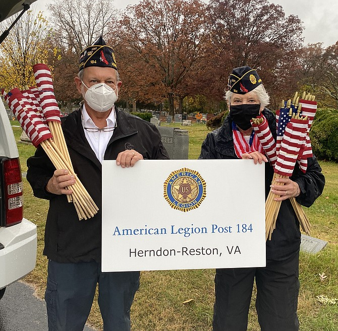 On behalf of The Wayne M. Kidwell American Legion Post 184 Herndon-Reston, Michael Cutler, Vice Commander, and Christine Cutler, Post Adjunct, prepare to install a modified Avenue of Flags.