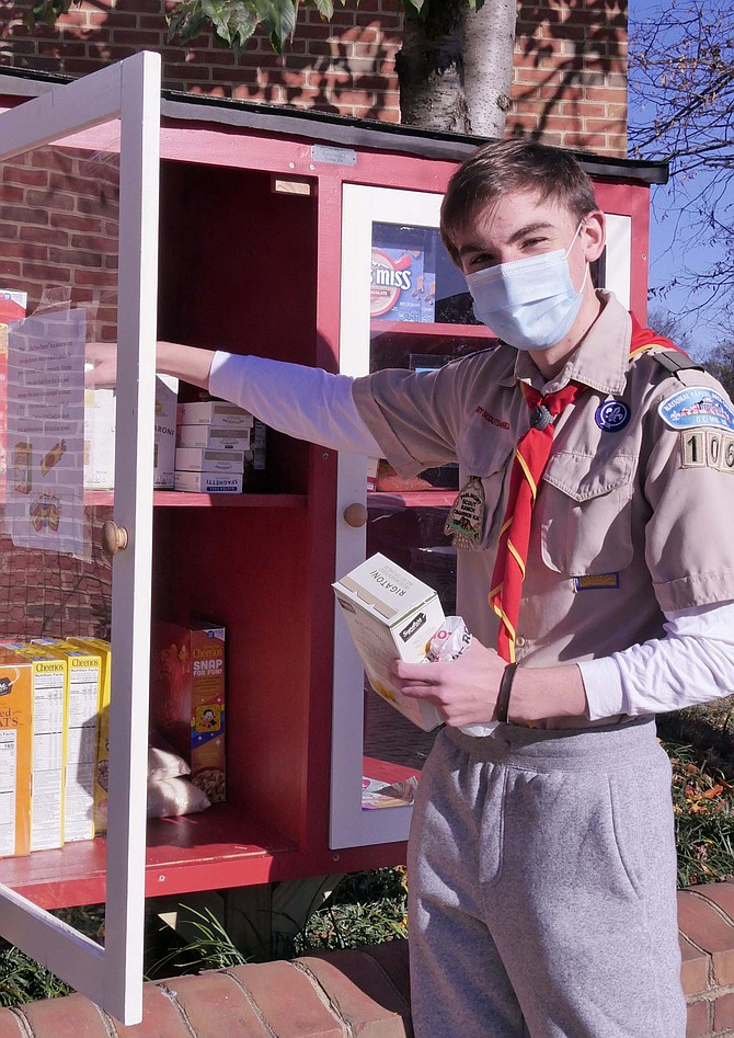 "On the morning of his Eagle Scout Review Board, Charlie Gaylord inspects the food donations in the ""Little Free Pantry"" that he constructed for his Eagle Scout Project."