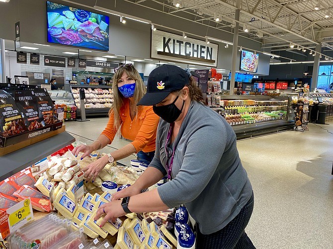 Cheese company vendor, Mary Lyon, Fredericksburg; and Giant employee, Jennifer Parker, Spotsylvania; arrange cheese products located near the spacious prepped foods kitchen area.