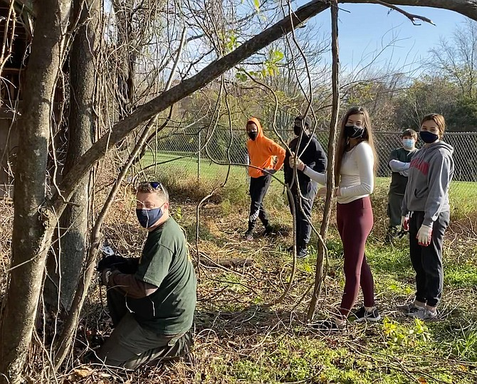 Laurel Hill Park volunteers clear invasive vines from a fence obscuring the historic turkey barn: Shawn Elklund, Justin Barnes, Joshua Miller, Livia Davidson, Grace Ametin, Caleb Elkund; also Nico Valckx (not pictured).
