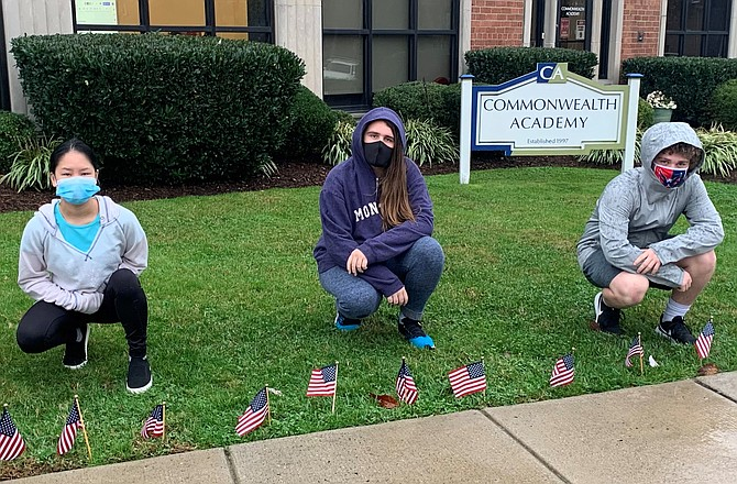 Students at Commonwealth Academy place American flags outside the school Nov. 11 in honor of Veterans Day.