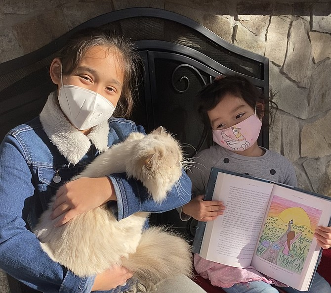 """Petra Demas, 10, of Great Falls holds Mima the family cat, as her little sister, Briella, 3, shows the kitty Petra's winning illustration featured in J.K. Rowling's book, """"The Ickabog."""""""