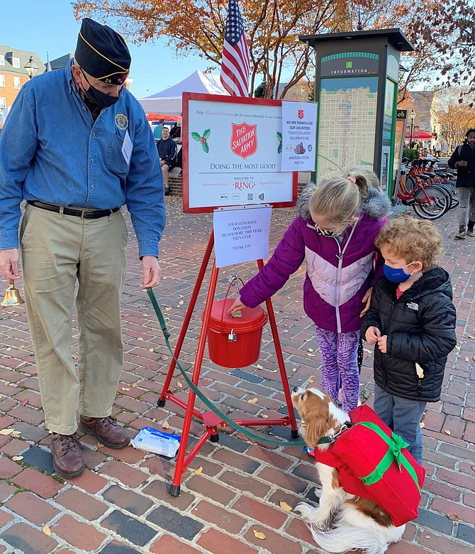 American Legion Post 24 Commander Henry Dorton, left, looks on as a donation is made to the Salvation Army Red Kettle Campaign Nov. 28 at Market Square. The annual donation drive runs through Dec. 24.