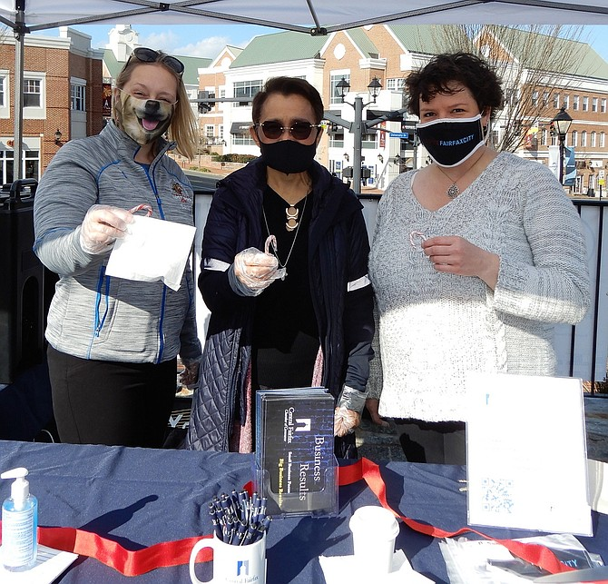 Manning one of the welcome stations, last Saturday in Fairfax City's Old Town Square, are (from left) Sarah White of the Lost Dog Café, Noa Gamboa of Small Biz Books & Accounts, and Jennifer Rose, executive director of the Central Fairfax Chamber of Commerce. They handed out muffins, hot chocolate, candy canes, face masks and pens.