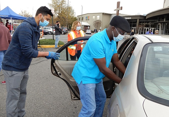 (From left) Arun Raj holds open a car door while Yomi Akinyemi, pastor of Zion Worship Center, places a food box inside.