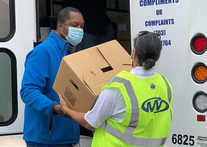 (On left) Paul Woods, from Fairfax County's Department of Neighborhood & Community Services, loads a Fastran bus with food for delivery.