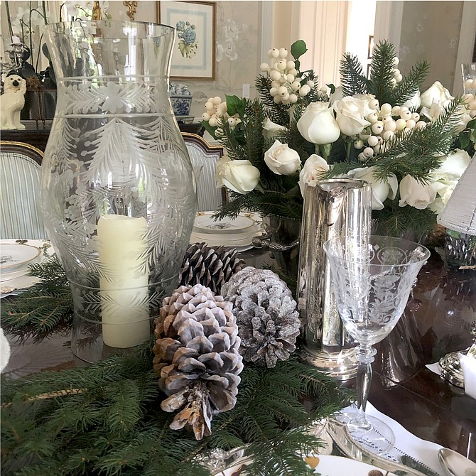 Etched hurricanes mixed with greenery and pine cones create an elegant tablescape.