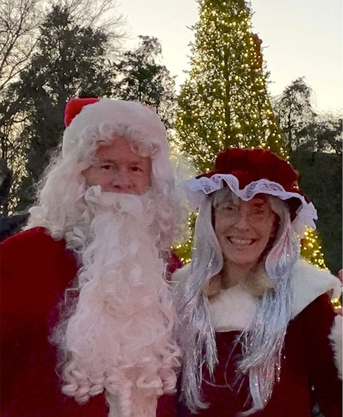 Santa and Mrs. Claus turn around to face their elves after lighting the tree.