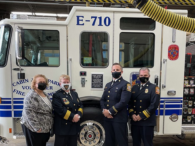 At the dedication of the new engine:  Mary Seavey, CJPVFD Chief Corinne Piccardi, James Seavy Jr. and Acting Fire and EMS Chief John A. Donnelly Sr. of the D.C. Fire Department, next to Cabin John's new fire truck at its dedication ceremony Saturday. The truck was dedicated in honor of former CJPVFD Chief James P. Seavey Sr.