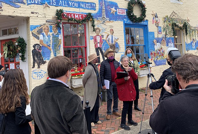 Nina Tisara, founder of the King Street Metro Enterprise Team, known as KSMET and the predecessor to the Old Town Business Association, makes remarks at the dedication of the Len Garon KSMET mural Dec. 4 at the corner of King and Fayette streets.