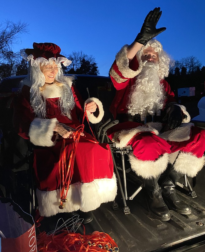 Santa waves from the back of the truck while Mrs. Claus untangles the bell necklaces for the elves to distribute to children in this year's Christmas Tree Lighting in Great Falls.