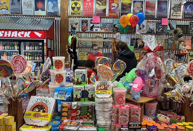Owner Tonya Kemp helps a customer check out on opening day of Rocket Fizz Soda Pop & Candy shop Dec. 11 in Fairlington Centre.
