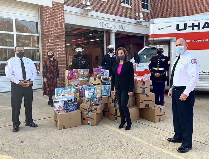 Fire Chief Corey Smedley, left, and Assistant Fire Chief Michael Cross, right, stand with members of the U.S. Marine Corps and Toys for Tots organizers after more than 2,000 toys were dropped off Dec. 10 at AFD headquarters for distribution to local families.
