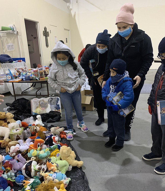 Attendees browse a selection of stuffed animals during the Firefighters and Friends toy distributions day Dec. 19 at My Father's House Christian Church International.