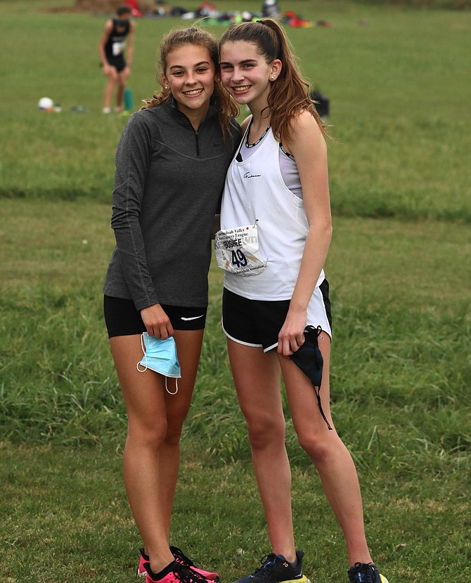 (From left)  Tea Geary, 15, of Herndon, teammate and friend, gives Gillian Bushée of Reston a hug after her winning cross country race.