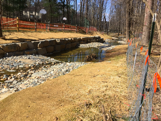 Fallsreach Restoration Project. A basketball court built in the floodplain was protected by armor-plating the stream bank. Note the total removal of plants and the newly engineered stream channel.