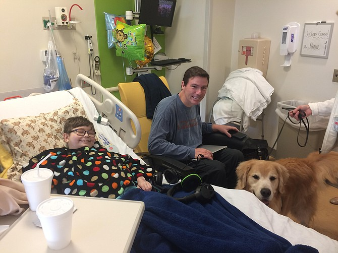 Gavin Smith of Great Falls and his dad, Keith, pictured during a canine visit at Johns Hopkins Children's Hospital. Mom Meg (not pictured) co-founded the nonprofit organization Cape Ivy.