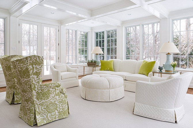 The Potomac, Maryland sunroom was redesigned by the Anthony Wilder team to include a coffered ceiling and classic green and white furnishings.