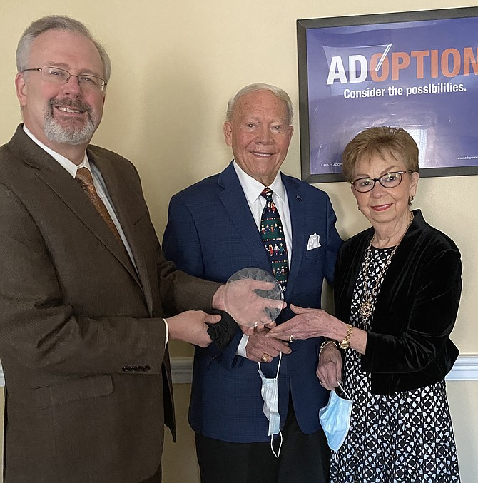 (From left) Chuck Johnson, President and CEO of the National Council For Adoption (NCFA) hands The Ruby Lee Piester  Award  to Linda Whitbeck Sharp of Mclean  and her husband,  Dr. Wayne Winston Sharp, Ph.D. The award is named after Ruby Lee Piester, founder of NCFA.