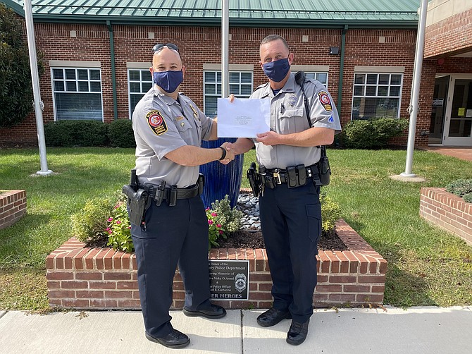 (From left) Assistant Station Commander Josh Laitinen presents the award to MPO Scott Bates outside the Sully District Police Station in Chantilly.