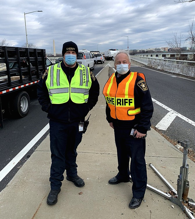 Alexandria Sheriff Dana Lawhorne, right, and Sheriff Lt. Daniel Gordon stand on the Virginia side of the 14th Street Bridge Jan. 19 as Alexandria Sheriff's Office deputies oversee the closure of the bridge during the Presidential Inauguration.
