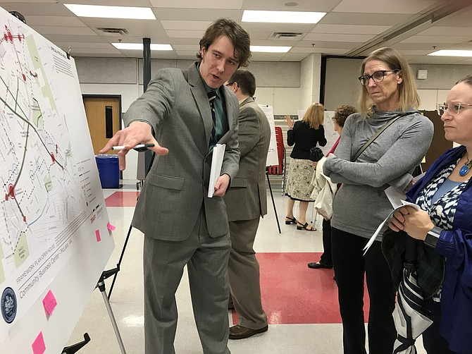 """On Sept. 27, 2018, when Streetsense presented the Framework Plan Open House for the CBC, Zachary Krohmal, Transportation Planner for Fairfax County Department of Transportation, looked at the display panels with McLean residents Carol Dinion and Erin Thiebert.  He said, """"Some ideas may be possible and doable; some may not."""" (File Photo)"""