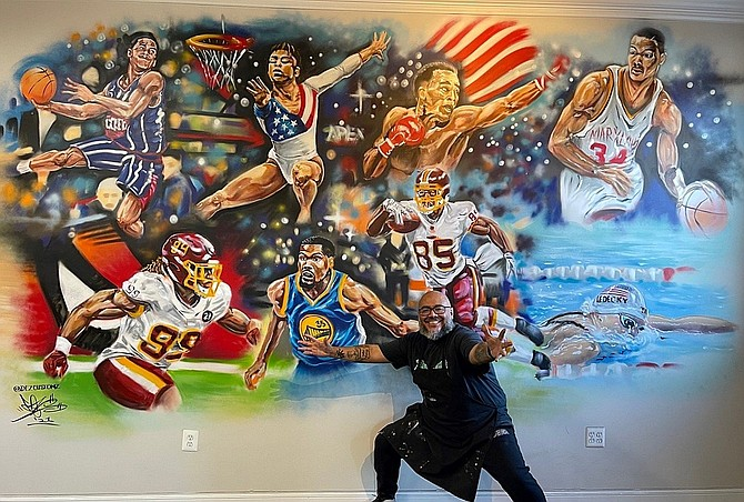 Famed artist DEZ Zambrano with his mural of star athletes.